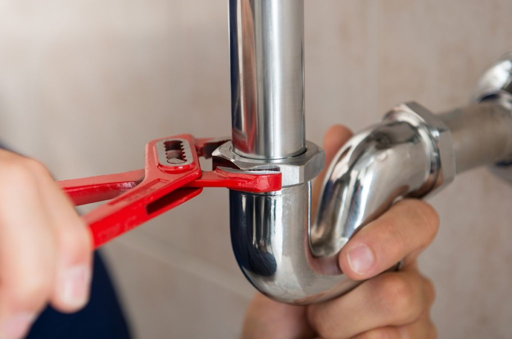 Plumber fixing a pipe with a wrench