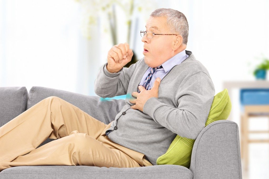 Photo of an elderly man coughing