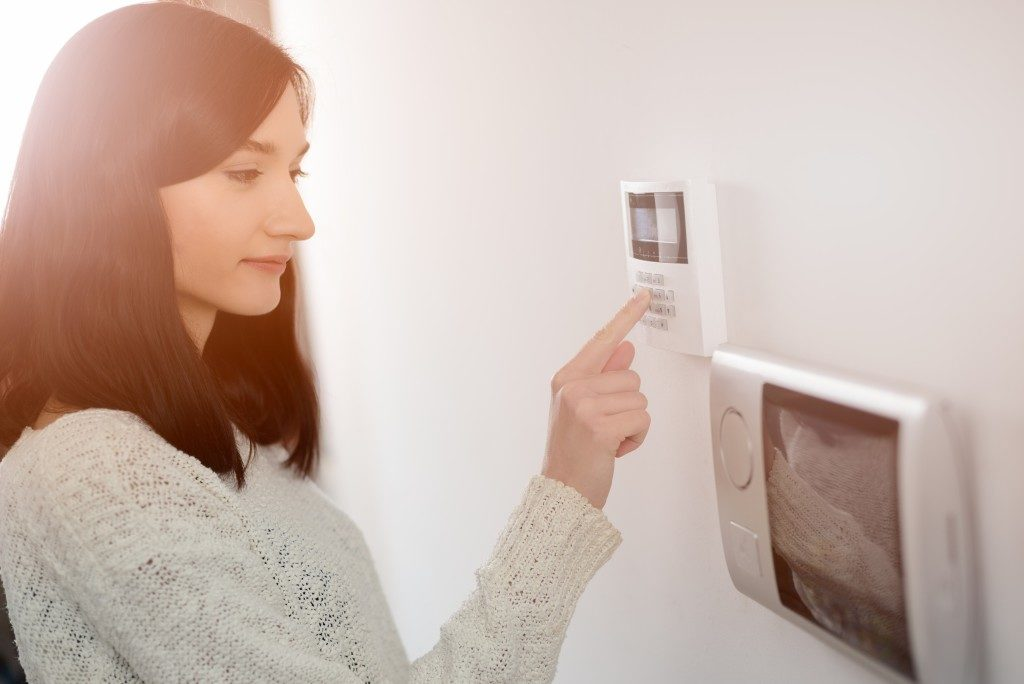 Woman using an alarm system