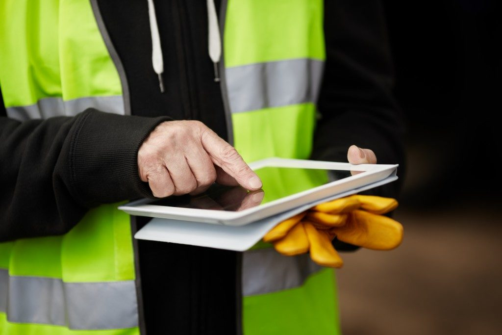 Construction worker using a tablet on site