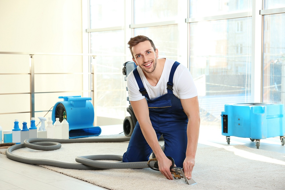 a man cleaning a carpet