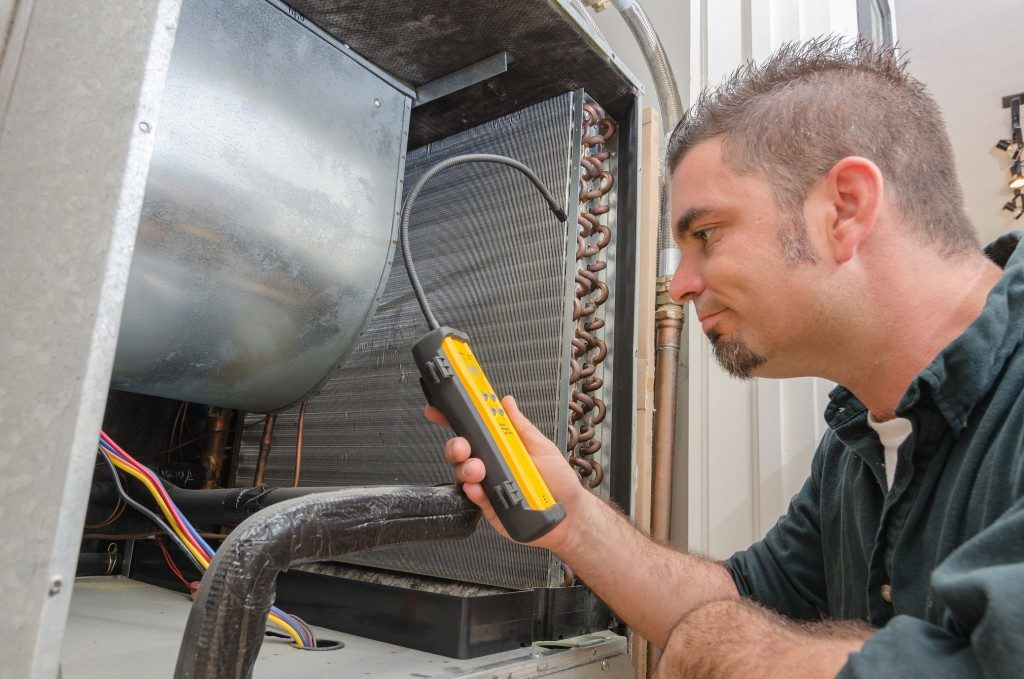 Worker looking for a refrigerant leak