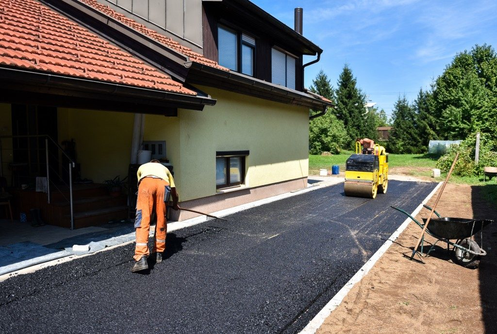 Worker working on an asphalt driveway