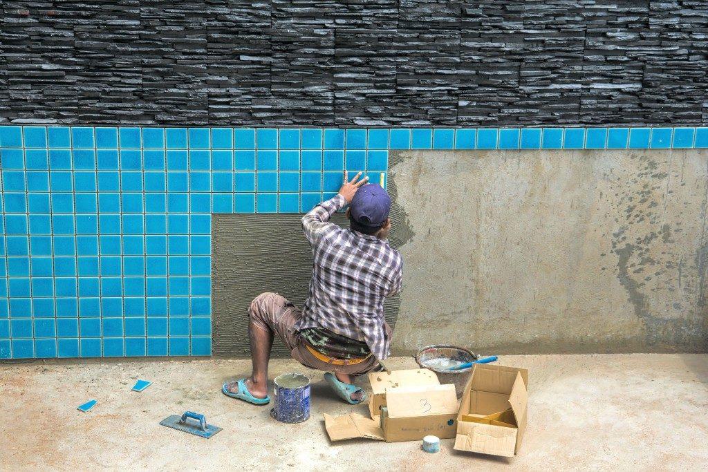 man applying pool tiles