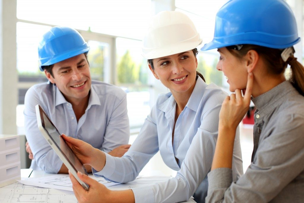 three people wearing hard hats while talking