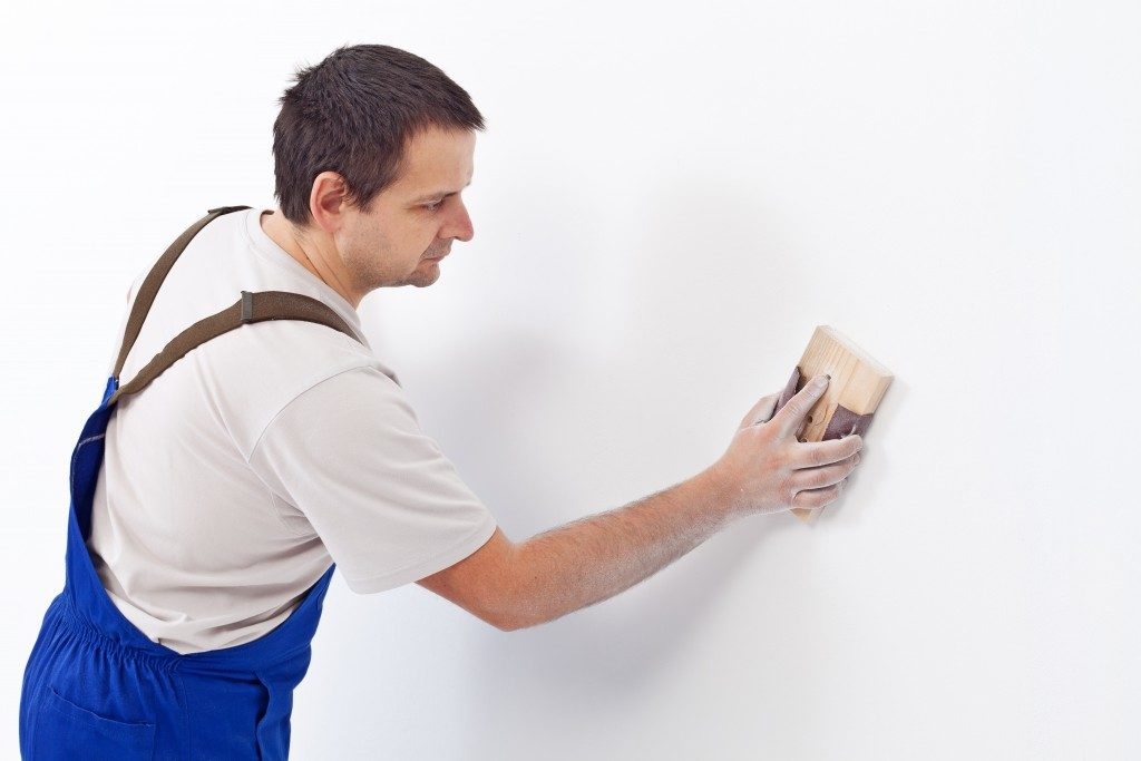Construction worker sanding the wall