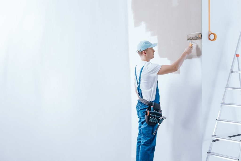 Worker painting the white walls