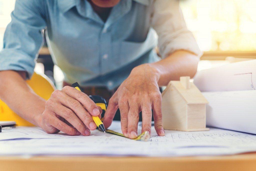 Man designing construction blueprint