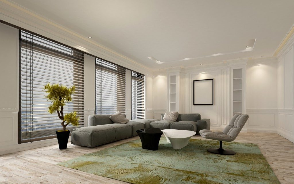 living room with windows located at the east side, green carpet and grey sofas
