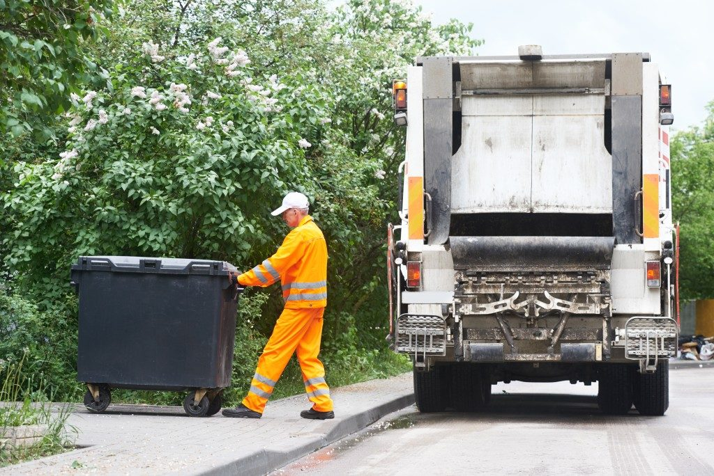 Garbage collector pulling the trash bin