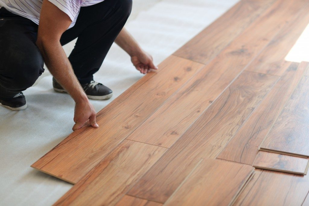 man installing wood flooring