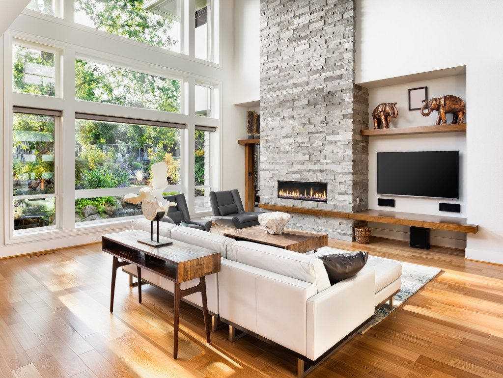living room with a glass window, in a wood flooring, cream sofa, and fireplace