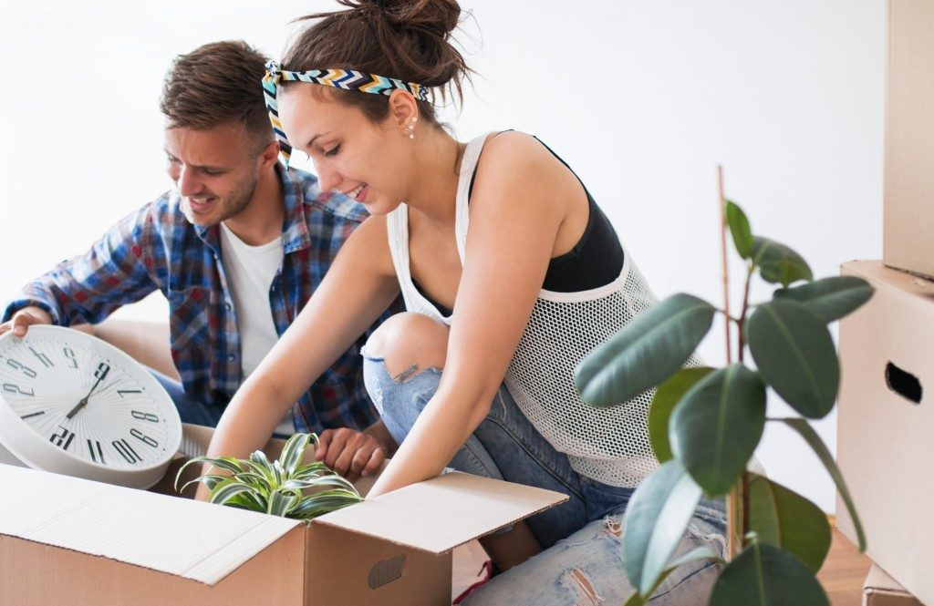 couple unpacking items in new home