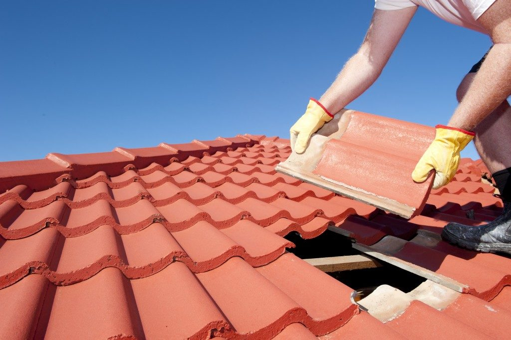 worker with yellow gloves replacing red tiles or shingles on house
