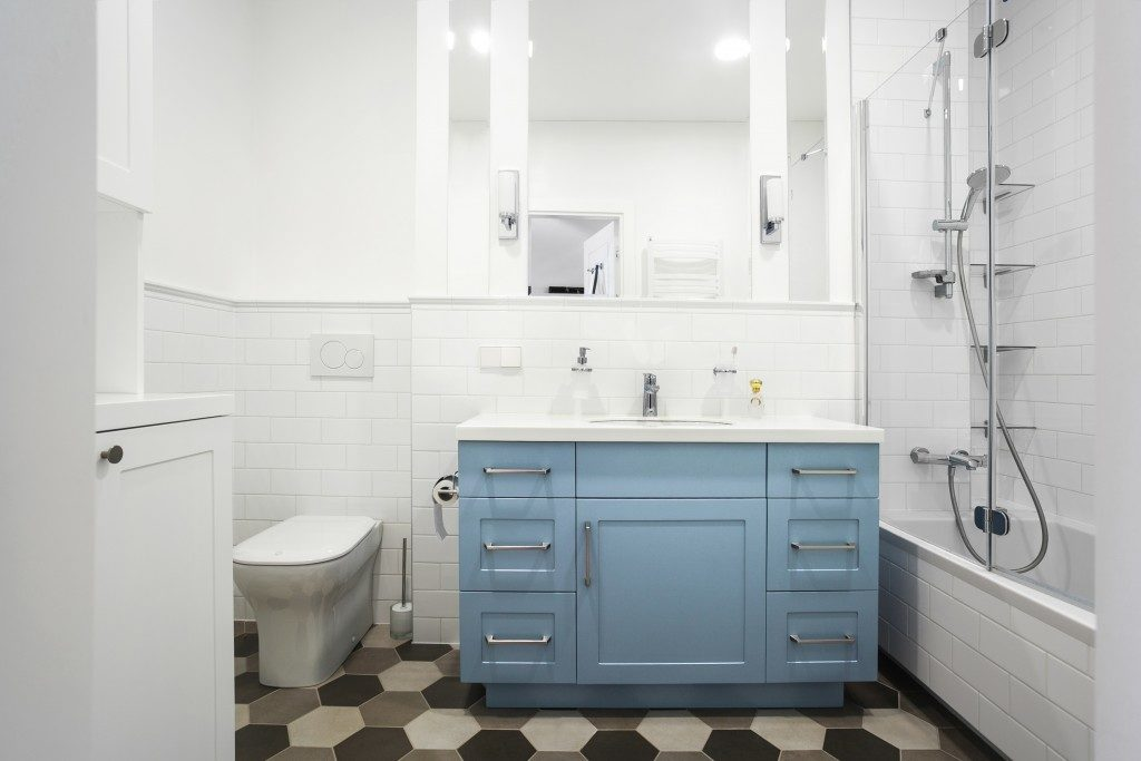 Small bathroom with blue cabinet