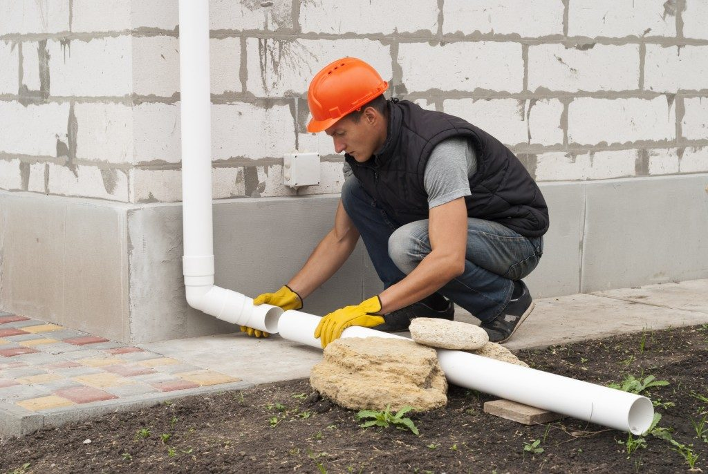 man installing an exterior drainage outside a house