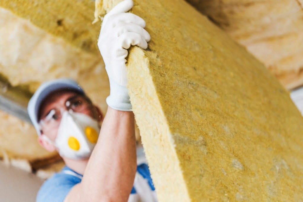Worker insulating a home