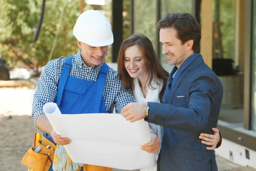 contractor showing paper to couple