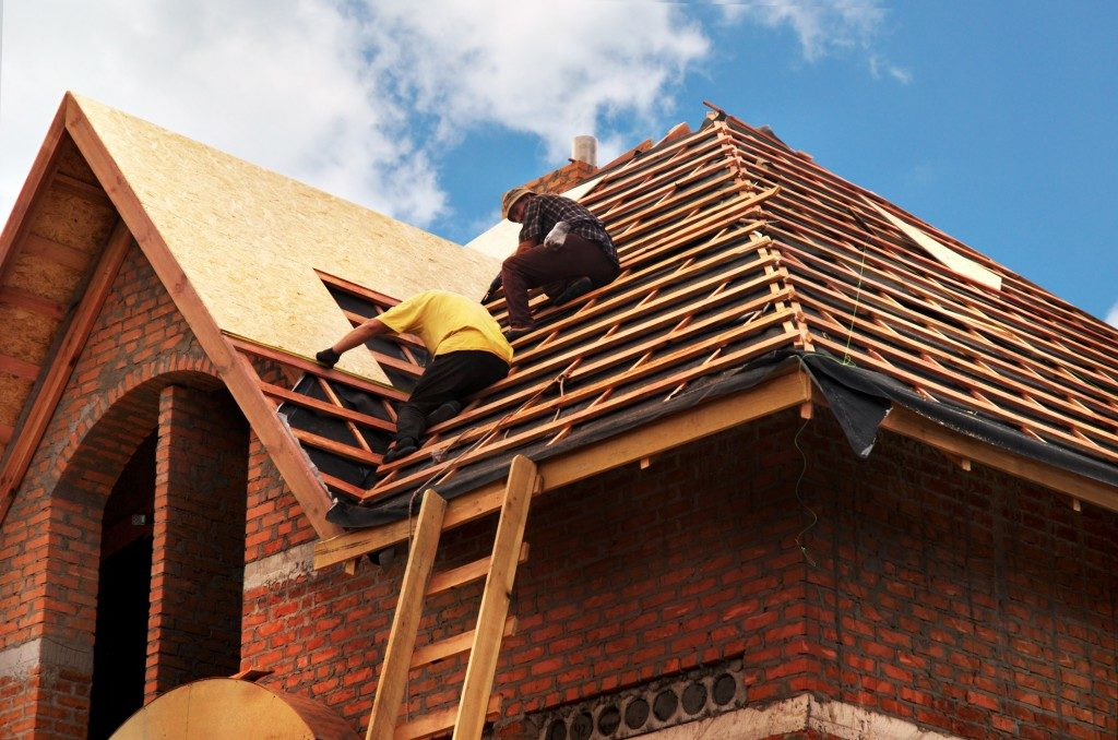 men building a roof over the house