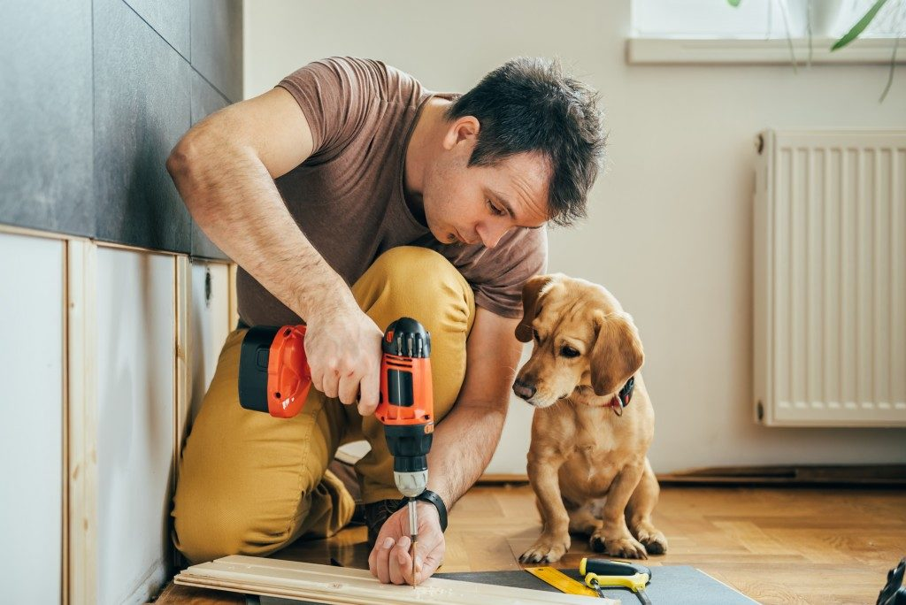 man doing construction work with his dog