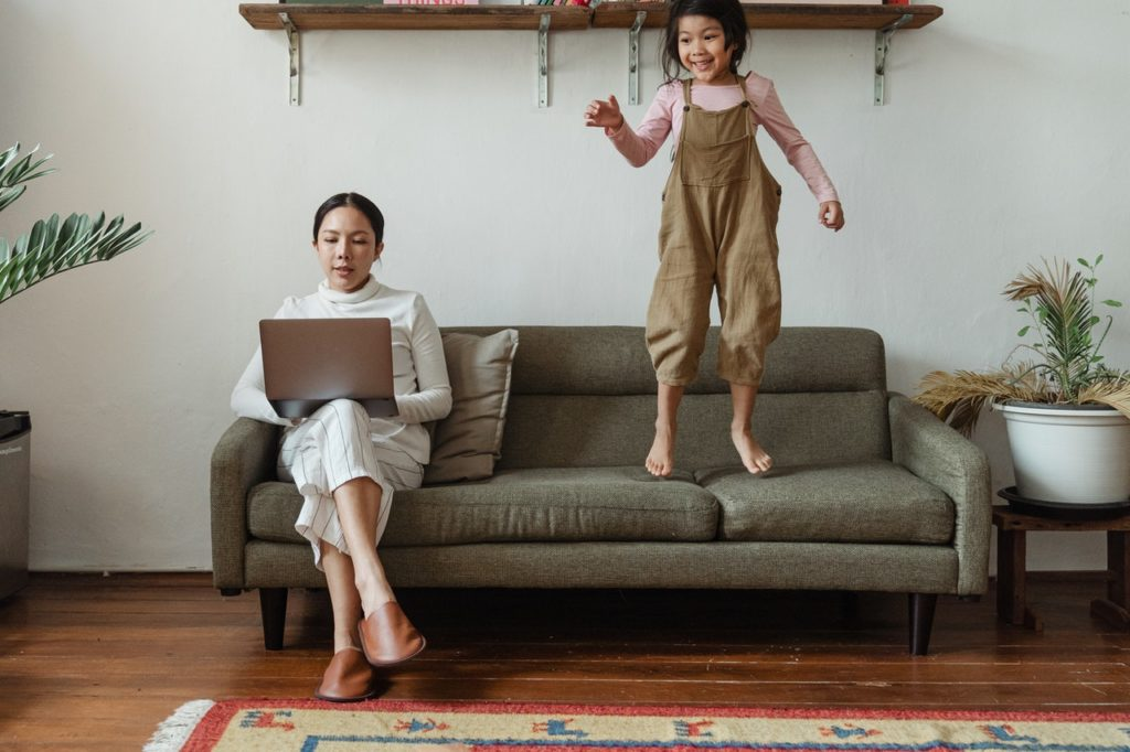 woman working from home on the couch with daughter jumping on couch