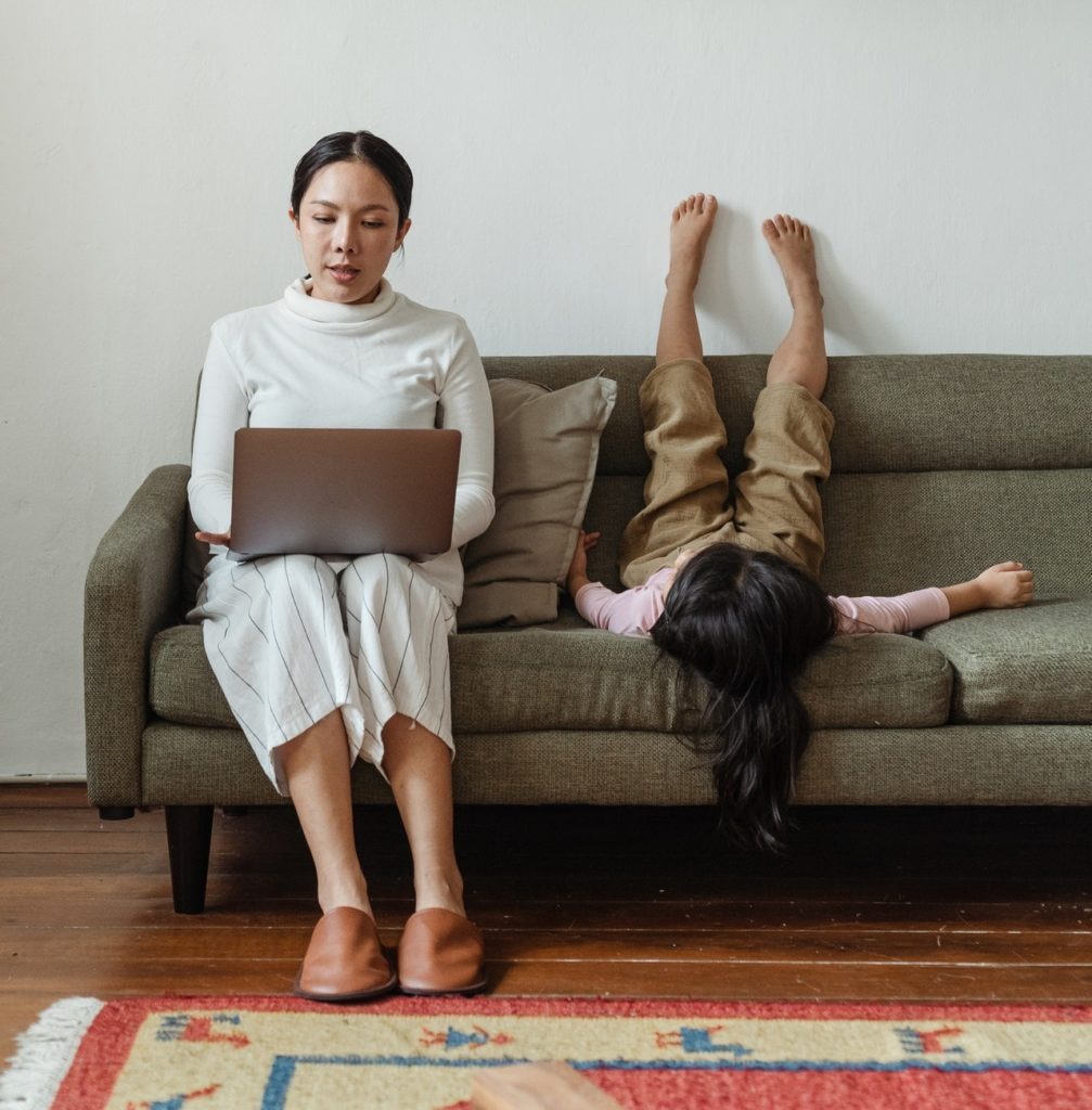 woman working from home on the couch with daughter